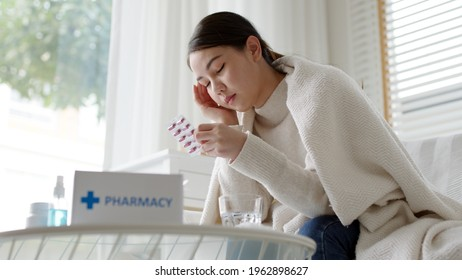 Sick asian woman sit under blanket acute severe headache on sofa at home. Female hold or check drug medicine capsule at home, suffer from flu. Cold or fever side effect after Covid19 vaccine shot.