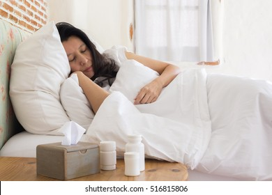 Sick asian woman sleeping in bed with high fever and medicine in foreground. (lens blur effect)