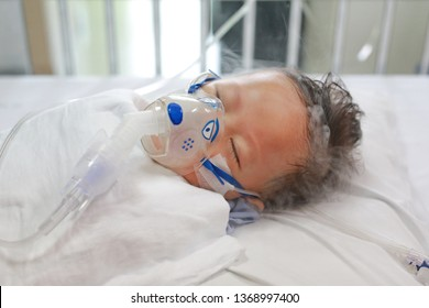 Sick baby boy applying inhale medication by inhalation mask to cure Respiratory Syncytial Virus (RSV) on patient bed at hospital.