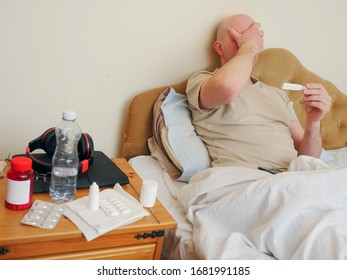 Sick bald man in his bed with thermometer, pills and water by his side. Concept flu, corona virus treatment.