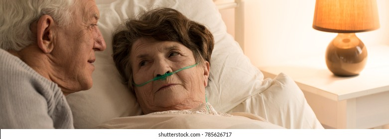 Sick, bedridden woman looking at her husband assisting her during illness at home
