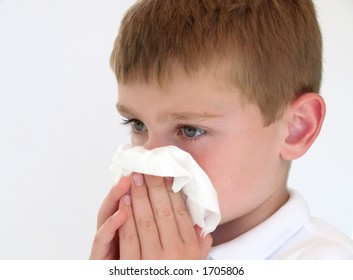 sick boy blowing his nose
