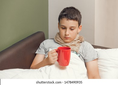 Sick boy at home recovering from flu and drinking hot tea.
