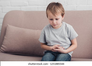 sick boy with stomach pain sitting on sofa in living room