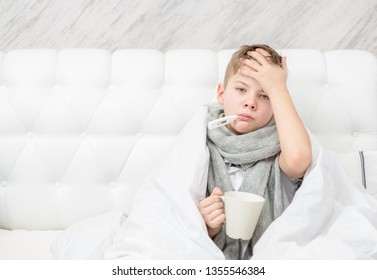 Sick boy with thermometer in his mouth sitting on the bed and holds cup. Empty space for text