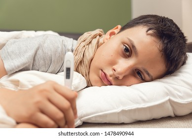 Sick boy with thermometer laying in bed. Sick child with fever and illness in bed. Flu. Cold