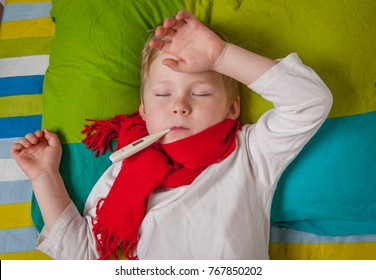 Sick boy with thermometer laying in bed and hand taking temperature. Child with a scarf on neck