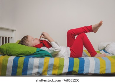 Sick boy with thermometer laying in bed and hand taking temperature. Child with a scarf on neck in bedroom