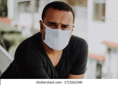 Sick  brazilian man wearing medical mask at home during Coronavirus outbreak