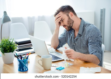 Sick businessman with temperature and headache working in office.