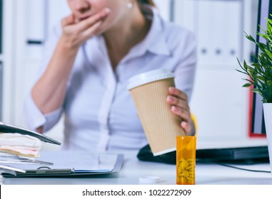 Sick businesswoman holding cup of coffee and medical pill at workplace, suffering from migraine headache, feeling bad, taking medicine at work, depressed woman addicted to antidepressant tablets.