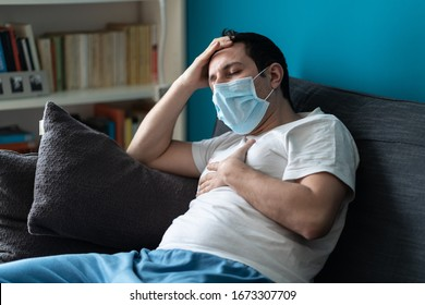 A sick caucasian Man wearing face mask feeling sick headache and cough because of Coronavirus Covid-19 on the sofa in quarantine
