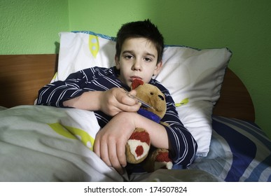 Sick child in bed with teddy bear. Measuring the temperature with a thermometer.