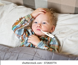sick child boy lying in bed with a thermometer in mouth and touch his forehead