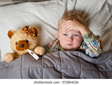 sick child boy lying in bed with toy bear and thermometer in mouth