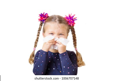 Sick child. Children's cold. Little girl has runny nose and blows nose into paper handkerchief. Children's cold, selective focus on handkerchief. Acute respiratory viral infection. Isolated on white