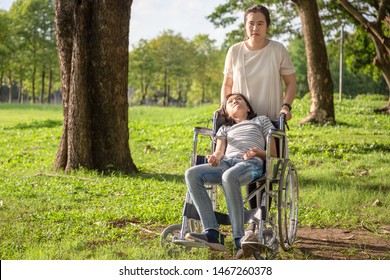 Sick child girl with cerebral palsy in wheelchair in outdoor park, daughter suffering from seizures,illness with epilepsy,asian mother or caregiver care of girl patient,brain,intellectual disability