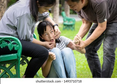 Sick child girl with epileptic seizures in outdoor park,daughter suffer from seizures,illness with epilepsy during seizure attack,asian mother,father care of girl patient,brain,nervous system concept