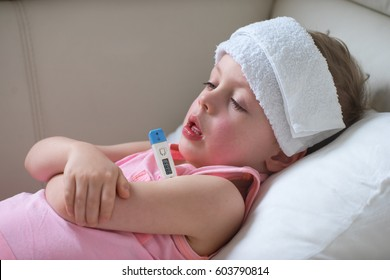 Sick child with high fever laying in bed and  holding thermometer.  Compress on forehead.