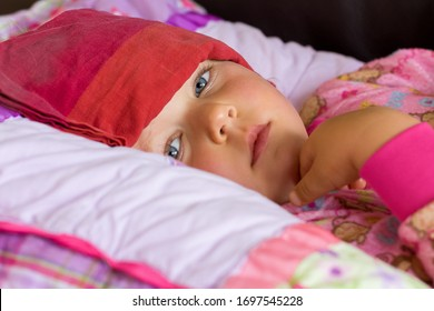 sick child looks miserably at camera while resting with a cold compress on forehead