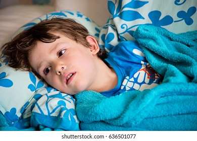 Sick child lying on couch at home having fever feeling ill. Getting well of flu.Kid with runny nose and sore throat