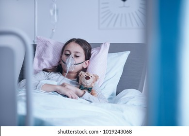 Sick child with oxygen mask during treatment in the hospital
