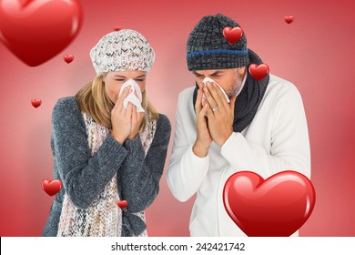 Sick couple in winter fashion sneezing against red vignette