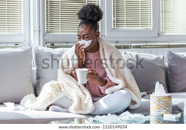 Sick day at home. African American woman has runny nose and common cold. Cough. Closeup Of Beautiful Young Woman Caught Cold Or Flu Illness. Portrait Of Unhealthy Girl Drinking Tea.
