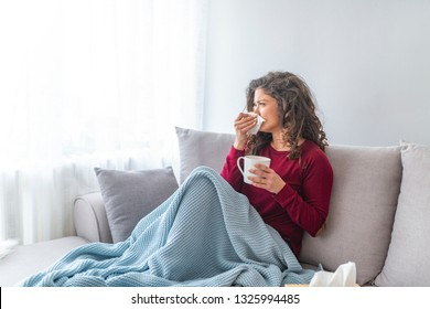 Sick desperate woman has flu. Rhinitis, cold, sickness, allergy concept. Pretty sick woman has runnning nose, rubs nose with handkerchief. Sneezing female. Brunette sneezing in a tissue