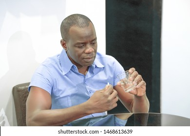 Sick elderly african man holding pill glass of water at home on the sofa. Depressed unhealthy man, about to take antidepressant pill, emergency contraceptive, painkiller for painful periods.