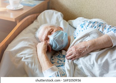 Sick Elderly Caucasian Woman Protective Mask on Face in Bed Eyes Closed. Quarantined During Virus Outbreak.Concept -  caring for health of elderly. Self-Isolation. Close up.