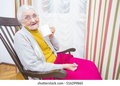 Sick elderly lady taking her medication with a cup of water.