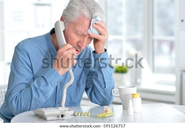 Sick elderly man calling by phone