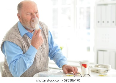 Sick elderly man makes inhalation