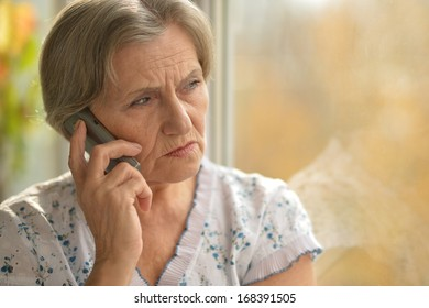 Sick elderly woman calling on phone at home