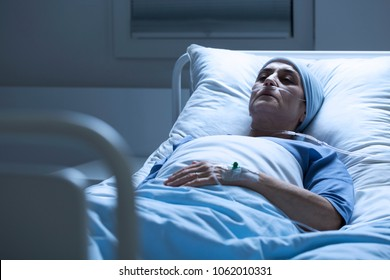 Sick, elderly woman with a headscarf and eyes closed dying alone of cancer in a hospital bed