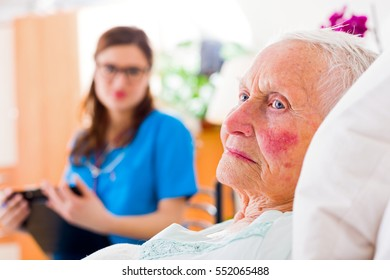 Sick elderly woman laying in bed, sympathizing doctor caring for her in the background.
