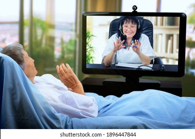 A sick elderly woman lies in bed and waves her hand to the telemedicine doctor on a large monitor.