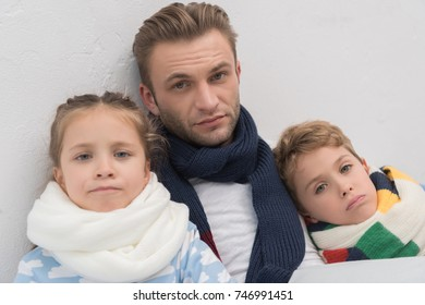 Sick family lying in a bed with scarfs over necks
