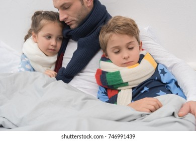 Sick father with children lying in a bed with scarfs over necks