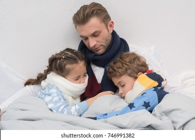 Sick father with son and daughter lying in a bed with scarfs over necks
