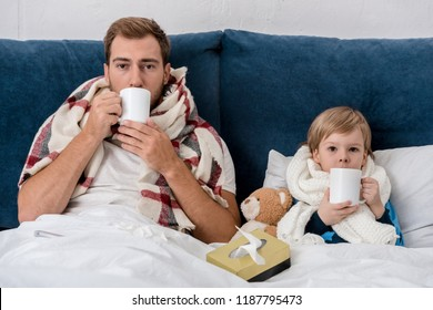 sick father and son in scarves drinking tea while sitting in bed and looking at camera