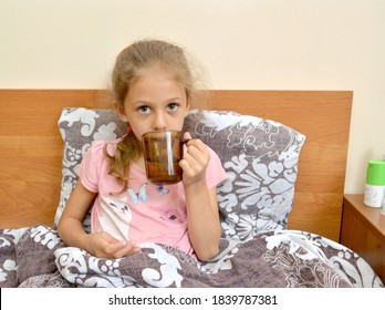 A sick girl drinks medicine with water from a mug, sitting in bed