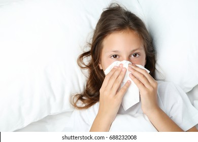 Sick girl with handkerchief lying in white bed