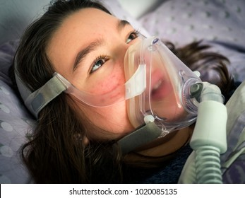 Sick girl in the hospital with an oxygen mask on her face