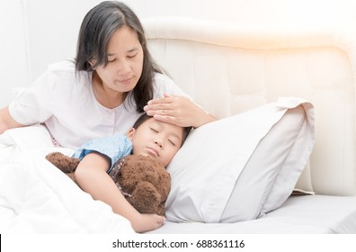 Sick girl laying in bed and mother hand taking temperature. Sick child with fever and illness in bed, healthcare concept