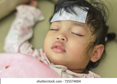 sick girl lying on bed,Asian little girl 3 year old sick lying in hospital.