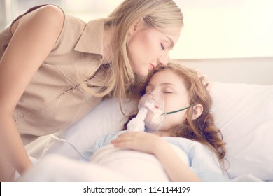 Sick girl lying on the hospital bed and her mom kiss to support.
