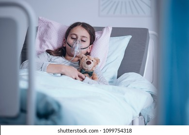 Sick girl with oxygen mask sleeping in a hospital bed with teddy bear