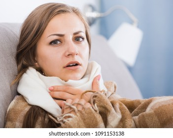 Sick girl with scarf on neck lying on sofa under blanket